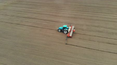 seeder : aerial survey, spring, a tractor with special precision planters is working in the field, there is a planting of corn, or sunflower. planting season on the farm. modern technologies in agriculture.