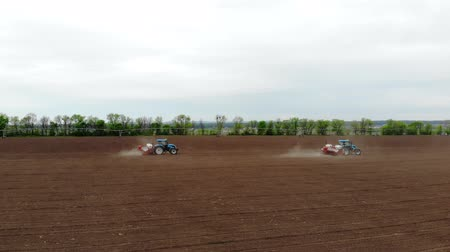 есть : aerial survey, spring, there are two tractors in the field with special precision planters, corn is planted, or sunflower. In field is irrigation system. sowing season on farm. modern technologies in agriculture.