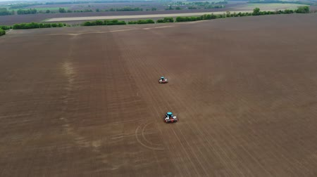 seeder : aerial survey, top view, spring, there are two tractors in the field with special precision planters, corn is planted, or sunflower. sowing season on farm. modern technologies in agriculture.