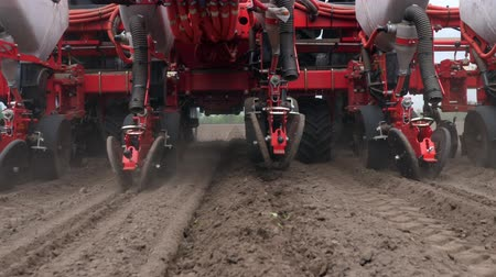 akkerland : close-up, tractor with special precision planters, seeder is working in the field, agricultural machinery is planting corn, or sunflower seed into freshly plowed land.