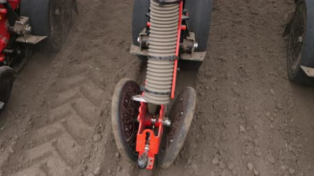 seeder : close-up, tractor with special precision planters, seeder is working in the field, agricultural machinery is planting corn, or sunflower seed into freshly plowed land.