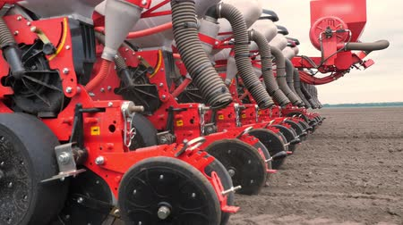 tiller : close-up, tractor cultivator cultivates, digs the soil. tractor plows the field. automated tiller for digging soil in farm into freshly plowed land. spring