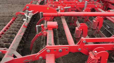 plowed land : close-up, tractor cultivator cultivates, digs the soil. tractor plows the field. automated tiller for digging soil in farm into freshly plowed land. spring
