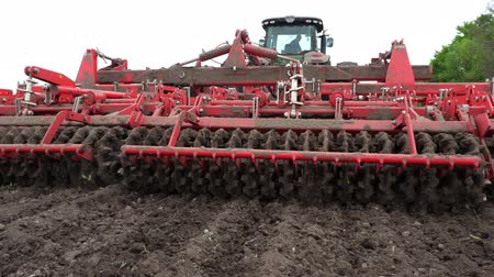 grass flowers : close-up, tractor cultivator cultivates, digs the soil. tractor plows the field. automated tiller for digging soil in farm into freshly plowed land. spring