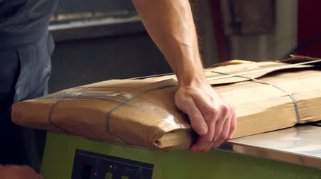 genişlik : packaging furniture products. close-up. The worker carefully wraps the furniture items in cardboard packaging, prepares them for transportation.