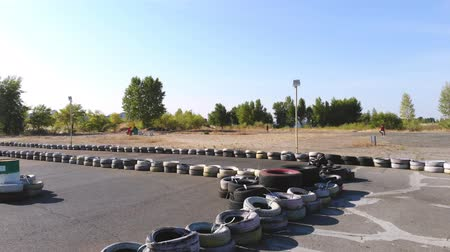 Young go cart race on circuit outdoors. There are safety barriers made of old wheels . Ten years old girl drives go-kart. Go-cart racing. Summer