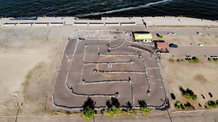Aero, top view. Go-cart racing on circuit outdoors. There are safety barriers made of old wheels. Summer