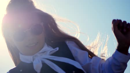 portrait. teenager girl in sunglasses dancing in the sun. her hair flutters in the wind.