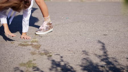 close-up. teenage girl legs in pink shiny sneakers. girl is making a gymnastic exercise, a cartwheel