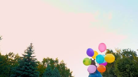 a teenage girl in jeans runs through the park with a large bunch of colorful balloons.