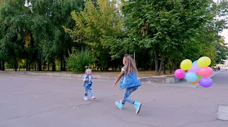 two little girls sisters, a teenage girl and a little one run towards each other in the park, with a large bunch of colorful balloons. They are huging
