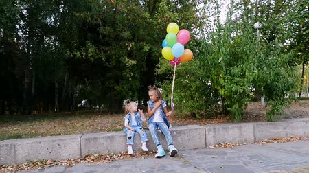 two little girls sisters, a teenage girl and a little one sitting on a bench in a park, with a large bunch of colorful balloons. They are talking Vídeos