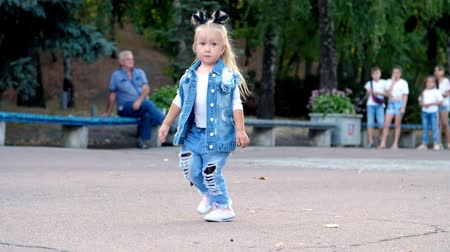 a little girl in a stylish denim suit and ponytails on her head walks through the park. Vídeos