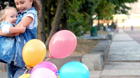 two little girls sisters in jeans suits, a teenage girl and a little one are huging in the park, with a large bunch of colorful balloons. They spin, twist merrily