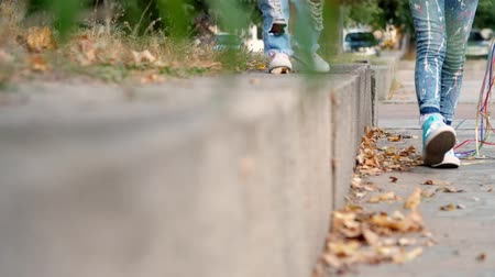 close-up, childrens feet in colorful and stylish sneakers and jeans. Children walk in the park. early autumn