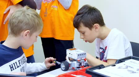 demirli : CHERKASY, UKRAINE, OCTOBER 19, 2019: school children, boys play with a toy designer, create various machines, robots of designer non-ferrous parts, colorful blocks. educational kids games. construction