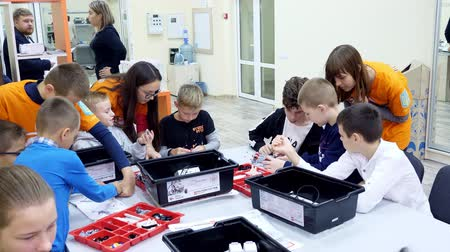 mobile game : CHERKASY, UKRAINE, OCTOBER 19, 2019: school children, boys and girls, work with a designer, create various machines, robots of designer non-ferrous parts, blocks. School of Robotics, STEM education.