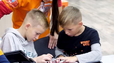 CHERKASY, UKRAINE, OCTOBER 19, 2019: school children, boys work with a designer, create various machines, robots of designer non-ferrous parts, blocks. School of Robotics, STEM education.