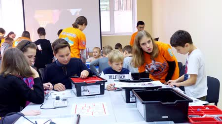 demirli : CHERKASY, UKRAINE, OCTOBER 19, 2019: students, children, boys and girls, create devices using the designer, non-ferrous parts, blocks, according to drawings in instructions on tablets. School of Robotics, STEM education.