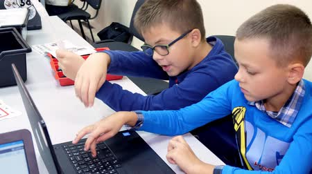 gimnazjum : CHERKASY, UKRAINE, OCTOBER 19, 2019: Schoolchildren working together on a laptop in computer class, typing on a keyboard. school and education