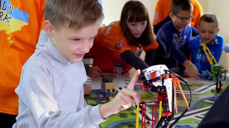 определенный : CHERKASY, UKRAINE, OCTOBER 19, 2019: boy plays with a robot made of small designer details. robot moves, can perform certain actions. educational lesson at school of Robotics, STEM education