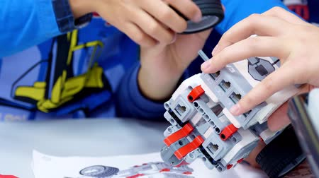 close-up, students create a device using the designer, non-ferrous parts, blocks, according to the drawings in the instruction. School of Robotics, STEM education.