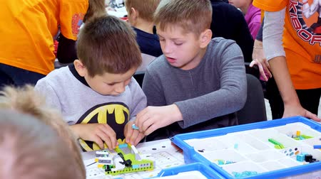 students, children, boys and girls, create devices using the designer, non-ferrous parts, blocks, according to drawings in instructions on tablets. School of Robotics, STEM education.