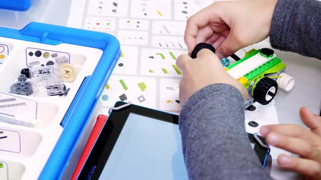 close-up, student creates device, machine, using the designer, according to the drawings in the instruction on the tablet . School of Robotics, STEM education