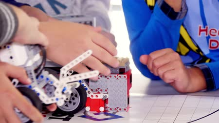close-up, children play with cars made from small parts of the designer. educational lesson at school of Robotics, with machines created from a designer. STEM education