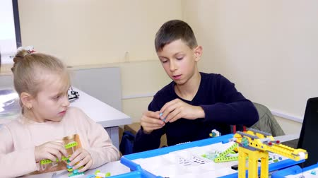 demirli : students, children, boys and girls, create devices using the designer, non-ferrous parts, blocks, according to instructions . School of Robotics, STEM education. Stok Video