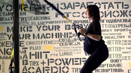 CHERKASY, UKRAINE, NOVEMBER 20, 2019: TRX training. young pregnant athletic woman, with a large belly, in a black tight-fitting tracksuit, is doing exercises with trx fitness straps in the gym