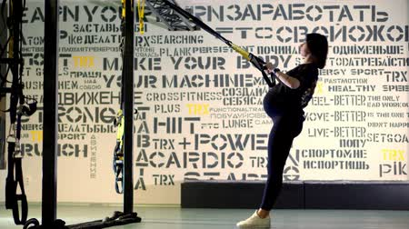 подвесной : CHERKASY, UKRAINE, NOVEMBER 20, 2019: TRX training. young pregnant athletic woman, with a large belly, in a black tight-fitting tracksuit, is doing exercises with trx fitness straps in the gym