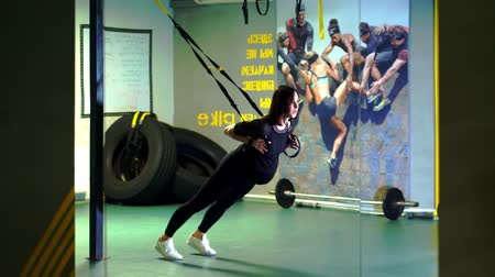 TRX training. young pregnant athletic woman, with a large belly, in a black tight-fitting tracksuit, is doing exercises with trx fitness straps in the gym