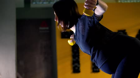 young pregnant athletic woman, with a large belly, in a black tracksuit, is doing exercises with dumbbells for arm muscles in the gym
