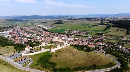 saxon : aero. panoramic view of the ancient castle, Rupea defense fortress placed on top of a hill. at the foot of castle there is a small town. Transylvania, Romania. sunny hot summer day