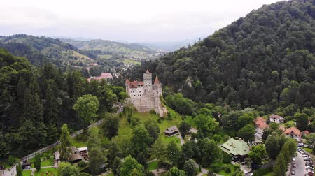 korumak : aero. panoramic view of the ancient Bran castle on a hill , Dracula Castle, Transylvania, Brasov, Romania. at the foot of the castle there is a small town. summer day Stok Video