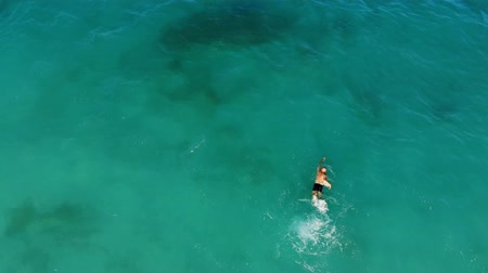 aero, top view. in the turquoise, blue waters of the sea, a man swims. summer hot sunny day