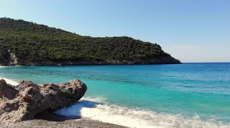 zante : beautiful beach of Evia island, Greece. sea bay with turquoise, blue water at the foot of the cliffs, among the mountains. soft waves with white foam at sea, summer hot sunny day