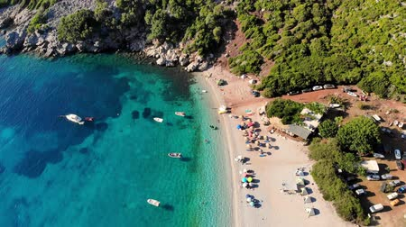 zante : aero. top view. beautiful summer seascape. wild beach of Evia island, Greece. sea bay with turquoise, blue water at foot of mountains. vacationers sunbathe on beach, many umbrellas,