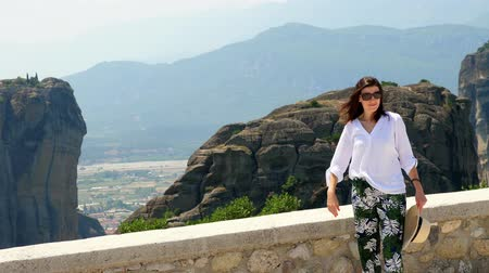evangelical : young woman admires the marvelous mountains of Meteora, Greece, wonderful landscape. Stock Footage