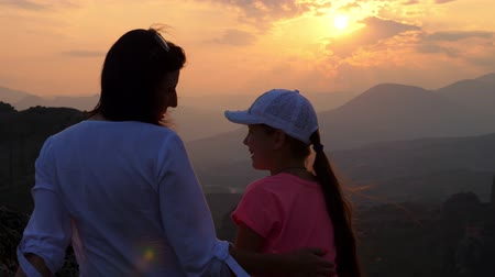 outlines of a woman and a teenage girl on a background of sunset in the mountains. Tourists admire the sunset in the Meteora mountains, Greece, in summer.