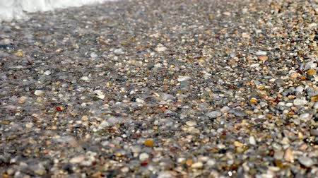 seixo : Close-up . soft waves, with white foam are washed ashore, on pebble beach. beautiful , multi-colored round sea pebbles on Mediterranean sea coast, shore. summer hot day. Greece Stock Footage