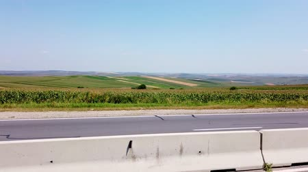 bulutsuz : road, autobahn, on the other side of the road are green fields. summer, cloudless day. view from the car window in motion.
