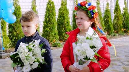 puericultura : CHERKASY REGION, UKRAINE, OCTOBER 10, 2019: portrait, children of eight years, a boy and a girl with flower wreath on her head, stand and hold bouquets, outdoors, in windy autumn weather.