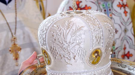 piskopos : CHERKASY REGION, UKRAINE, OCTOBER 10, 2019: close-up, on a tray they hold an elegant Orthodox priests hat , a white mitre, an olemn headgear of the orthodox bishop