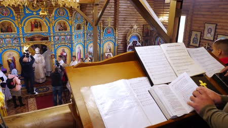 обряд : CHERKASY REGION, UKRAINE, OCTOBER 10, 2019: close-up, Orthodox christian priest reading church book. church ceremony. the consecration rite of newly built Church Стоковые видеозаписи