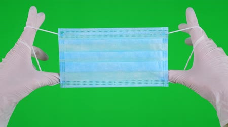 plastische chirurgie : close-up. hands in medical white gloves hold Medical blue color mask for protection against flu, respiratory diseases. on a green background
