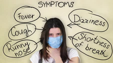 fájó : cold and flu symptoms. coronovirus symptoms. a sick girl in a blue medical bandage coughs, shows a headache, poor health Stock mozgókép