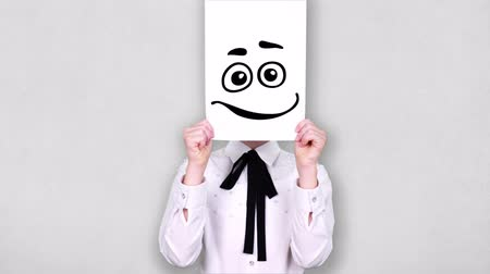 caricatura : portrait, teenager holds white paper sheet with happy smiley drawing, animation, covering face. emotions, Imagination, creativity, successful idea concept. Stock Footage