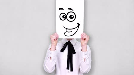 карикатура : portrait, teenager holds white paper sheet with curious smiley drawing, animation, covering face. emotions, Imagination, creativity, successful idea concept.